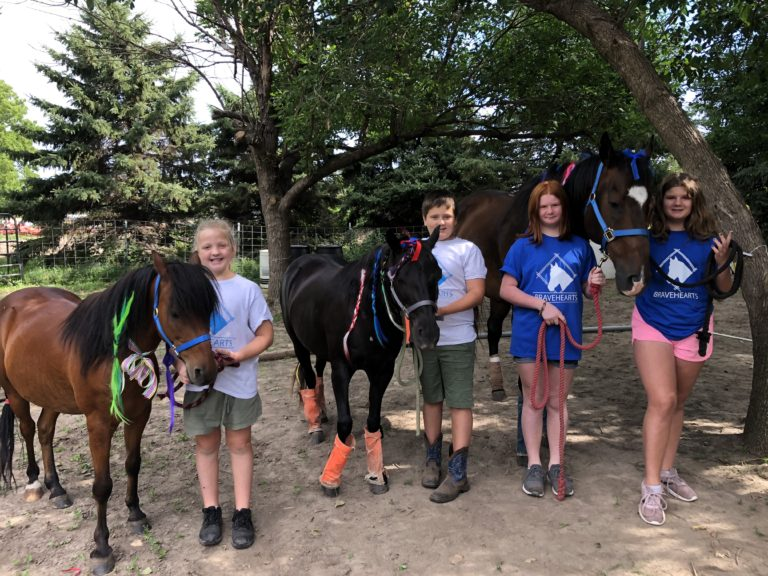 Group of kids participating in the Bravehearts program pose with horses.