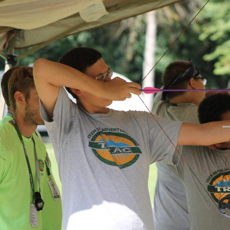 Teen boys practice archery as part of Teen Reach Adventure Camp
