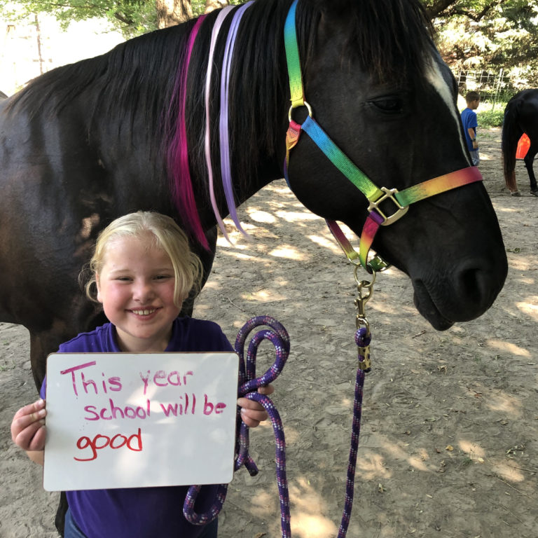 A girl holds up a hand-made thank you sign while standing in front of a horse. She is participating in Bravehearts equine program in Kearney, NE