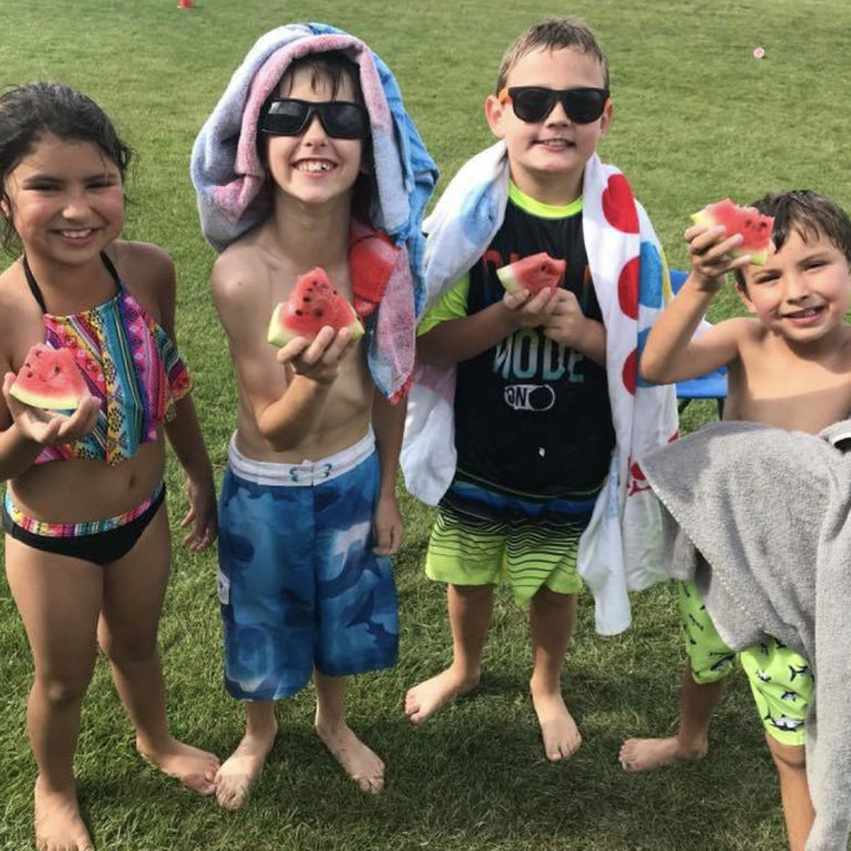 Children hold watermelon and smile for the camera at Alliance Recreation Center