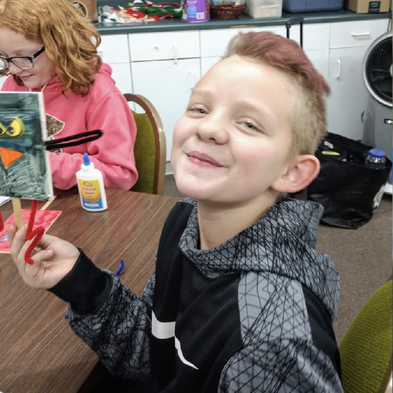 A boy smiles at the camera while participating in a program at the Carnegie Arts Center in Alliance, NE