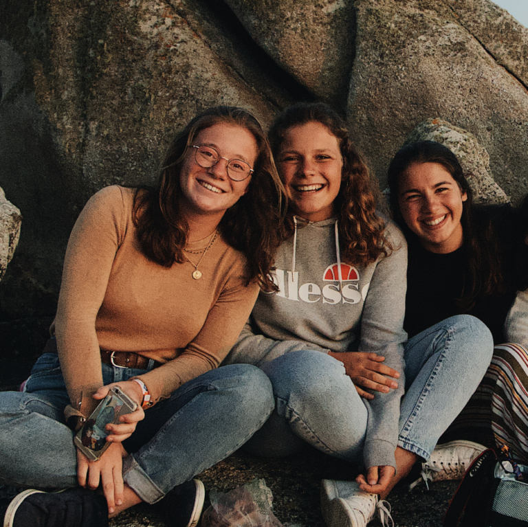 Three teen girls smile in front of rock.