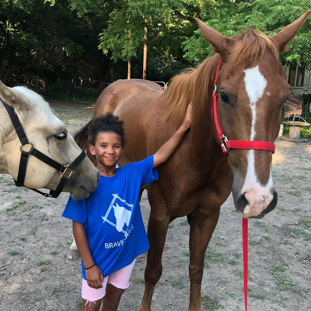 Young girl stands between two horses with her arm reaching up to pet one of the horses. Image from Bravehearts Equine Therapy.